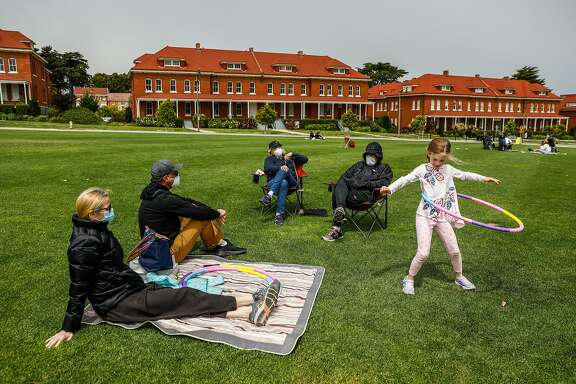 (L-r)Christina Dam, Jason Muscat, Becky Muscat and Bob Muscat watch as daughter and granddaughter Angie Muscat, 6, hula hoops while maintaining social distancing at the Main Parade Grounds in the Presidio in San Francisco, California on Sunday, April 26, 2020. Public health officials had feared spring-like weather over the weekend would cause a rush of people to set aside shelter in place mandates and descend upon public parks and beaches, putting themselves at risk to coronavirus exposure.