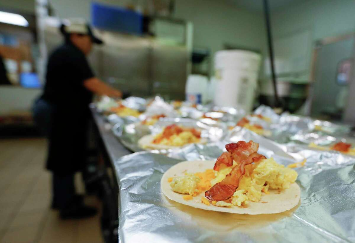 Breakfast tacos are prepared for to-go orders at Mckenzie's Barbeque and Burgers, Friday, April 24, 2020, in Conroe.