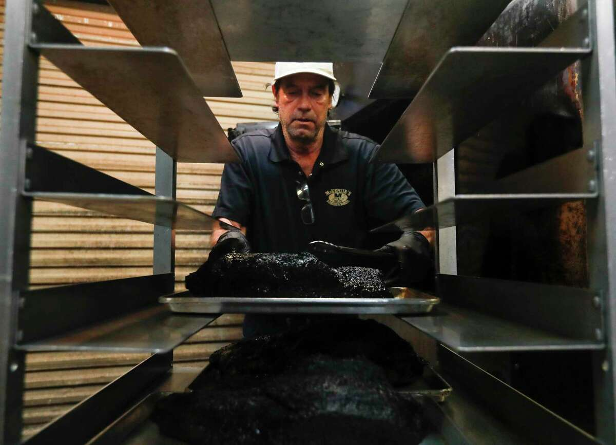 George Kimbrough pulls freshly cooked briskets out for to-go orders at Mckenzie's Barbeque and Burgers, Friday, April 24, 2020, in Conroe.