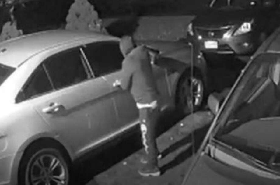 An alleged burglar caught on camera at 4 a.m., checking for unlocked car doors in a Trumbull, Conn., driveway recently Photo: Contributed Photo / Trumbull Police Department