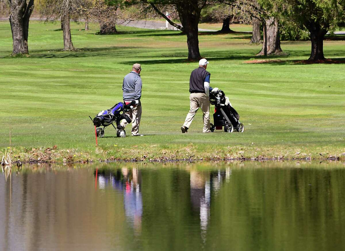 A couple golfers are seen social distancing and pulling their bags on carts at Western Turnpike Golf Course on Tuesday, April 28, 2020 in Guilderland, N.Y. (Lori Van Buren/Times Union)