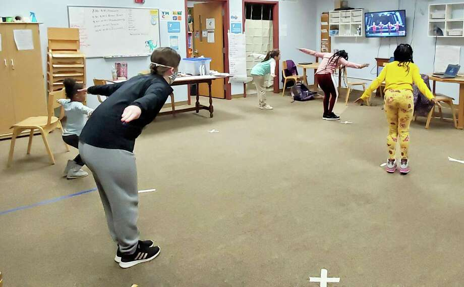 """Children enrolled in the Middlesex YMCA emergency child care program in Middletown take part in """"brain break"""" exercises Tuesday morning using the Just Dance video game. Photo: Contributed Photo"""