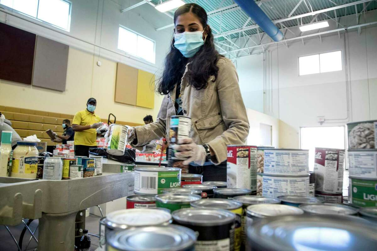 Ashley Khan sorts canned goods as she works to sanitize and sort dry goods on Thursday, April 16, 2020 at the Julia C. Hester House recreation center in Houston. Harris County Commissioner Rodney Ellis is teaming with the Houston Food Bank to provide food to residents impacted by coronavirus.