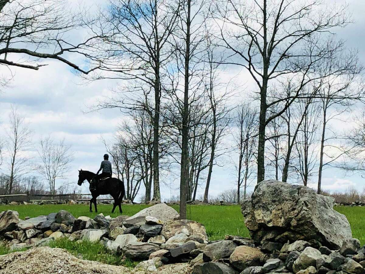 A person rides a horse at a property on Vail Lane in North Salem, N.Y.