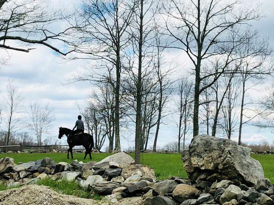 A person rides a horse at a property on Vail Lane in North Salem, N.Y. Photo: Lindy Olszewski