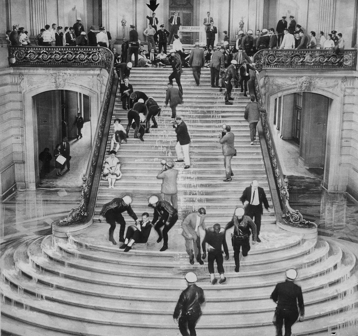 Police blast protestors with fire hoses, and the remove demonstrators from City Hall steps, April 13, 1960