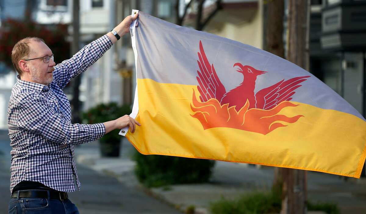 Brian Stokle waves a flag he designed as an alternative to the official city flag in San Francisco, Calif. on Tuesday, April 28, 2020. Stokle's design features a new Phoenix rising from flames on a gray and yellow background.