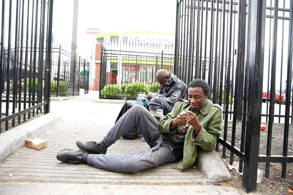 Local men who are homeless hang out on Main Street in downtown Houston in mid-March.