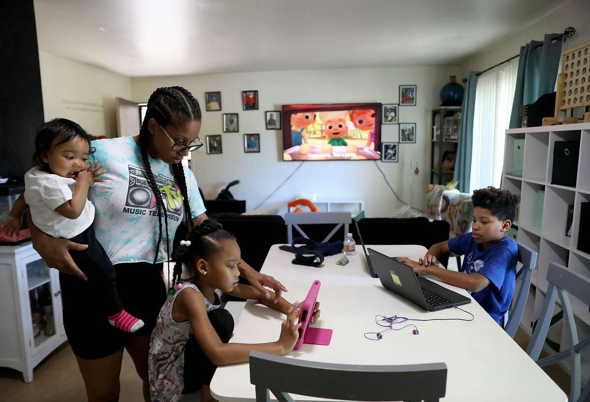 Kenya Pierce, 30, holds her 13-month-old baby Nyeri Rutherford as she helps her daughter, Nairobi Banks, 7, with her math lesson, while son Dannon Lemon, 12, works on his computer in their home on Tuesday, April 28, 2020, in Richmond, Calif. Pierce, who formally worked for WIC for nine years, is currently receiving WIC benefits.