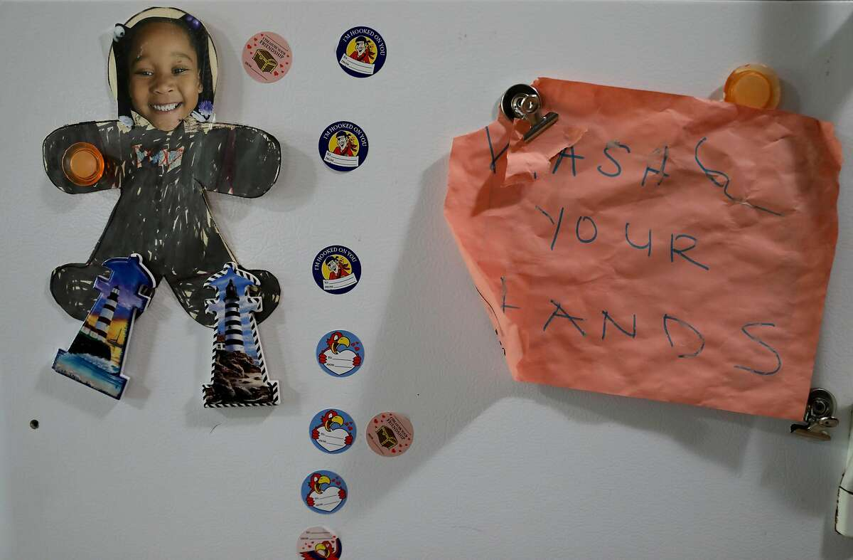 """A photo of Kenya Pierce's daughter is displayed on the refrigerator along side a note stating, """"Wash Your Hands,"""" in their home on Tuesday, April 28, 2020, in Richmond, Calif. Pierce, who formally worked for WIC for nine years, is currently receiving WIC benefits."""