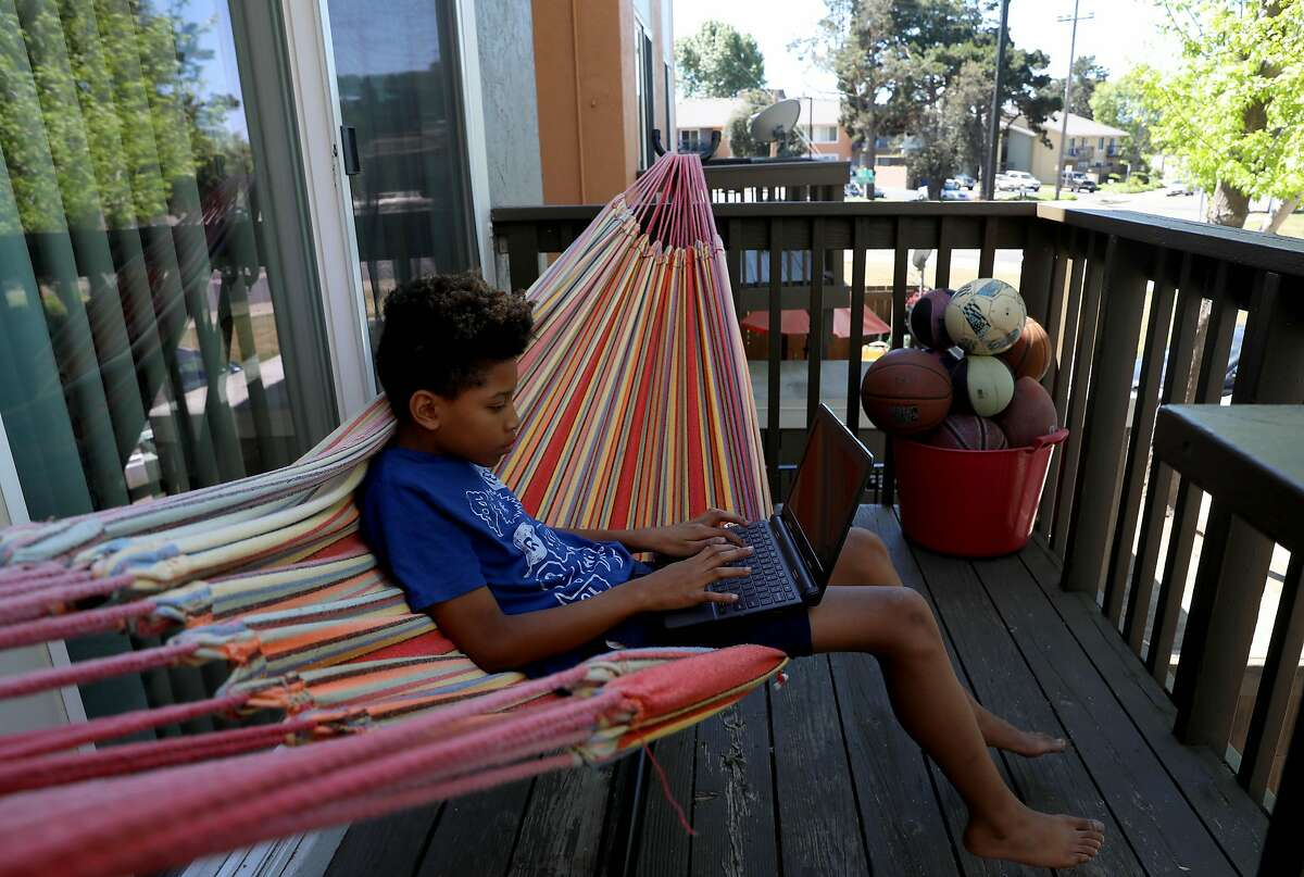 Kenya Pierce's son Dannon Lemon, 12, quietly works alone at their home on Tuesday, April 28, 2020, in Richmond, Calif. Pierce, who formally worked for WIC for nine years, is currently receiving WIC benefits.