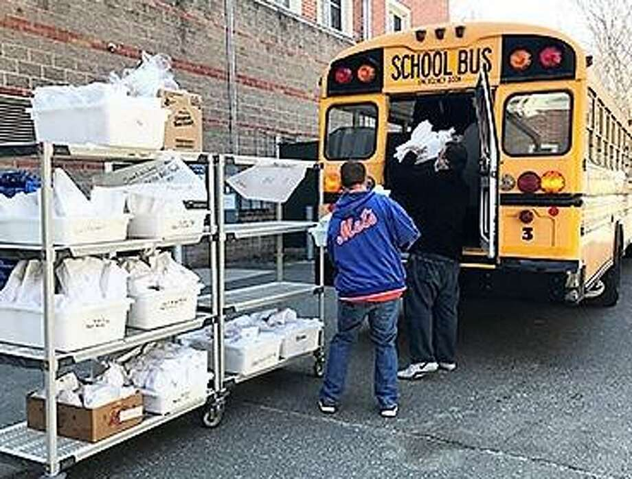Meals are loaded onto a school bus and will be brought to stops where Ansonia parents and guardians can pick them up. Photo: Contributed Photo
