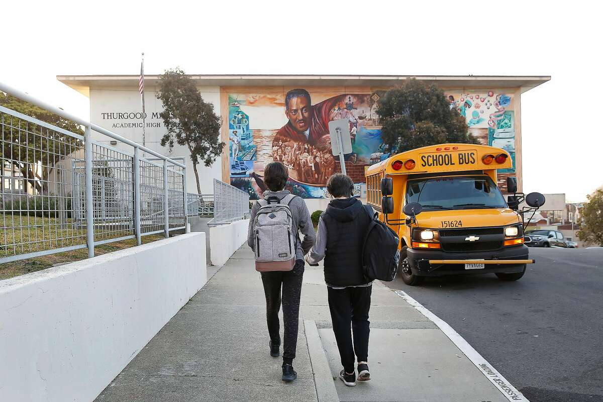 Isaac Conde (l to r), 14, and Joshua Conde, 16, walk toward Thurgood Marshall Academic High after their mother Laura Conde (not shown) dropped them off at school in the morning on Friday, March 13, 2020 in San Francisco, Calif.