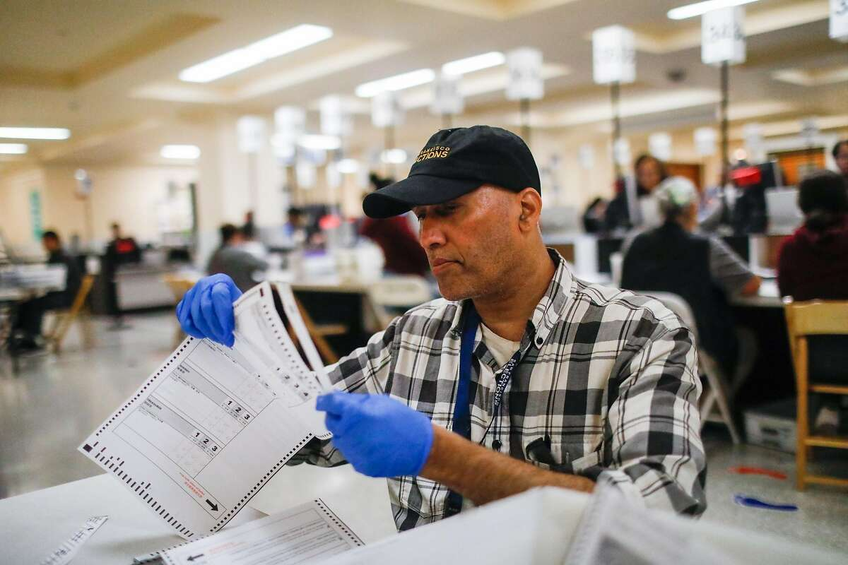 Luis Mascarenhas (center) organizes and count absentee and mail-in ballots at the Department of Elections at City Hall in San Francisco, California, on Wednesday, Nov. 6, 2019.