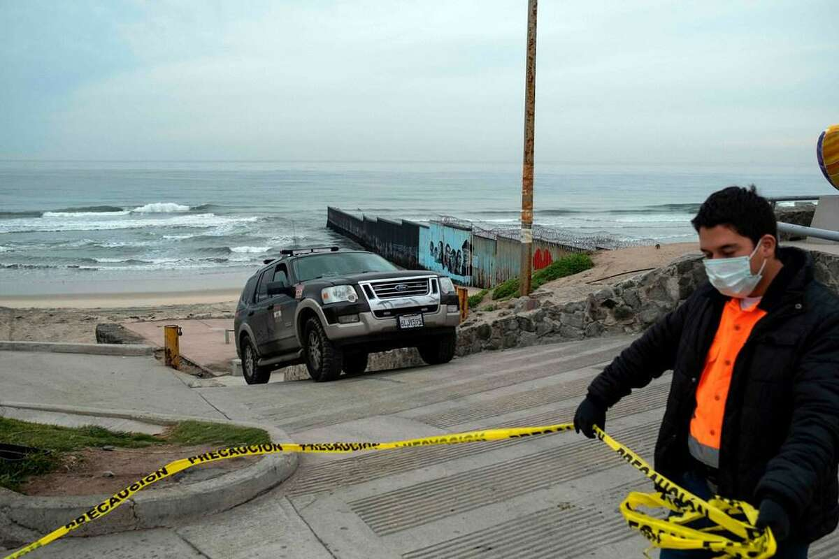 A volunteer places a caution line as the beach remains closed to the public, near the Mexico-US border fence in Playas de Tijuana, Baja California state, Mexico, on March 31, 2020. - The Mexican government declared a health emergency March 30 due to the coronavirus pandemic as the number of COVID-19 cases increases in the country, while Baja California state government intensified restrictions on people's mobility and the shutdown of beaches and commercial centers, among other non essential business.