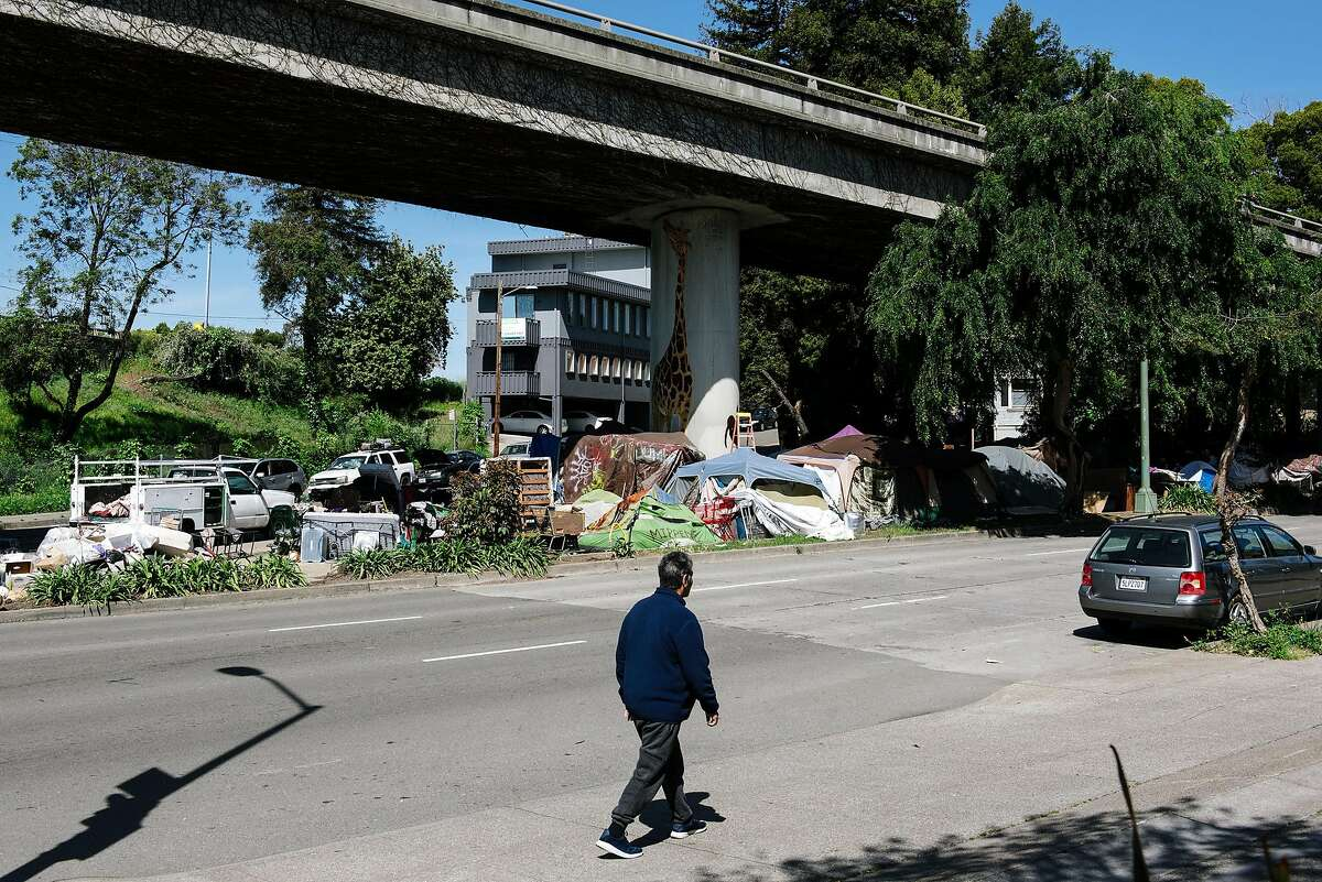 A person walks past a homeless encampment underneath Interstate 580 in Oakland, Calif, on Friday, April 22, 2020.