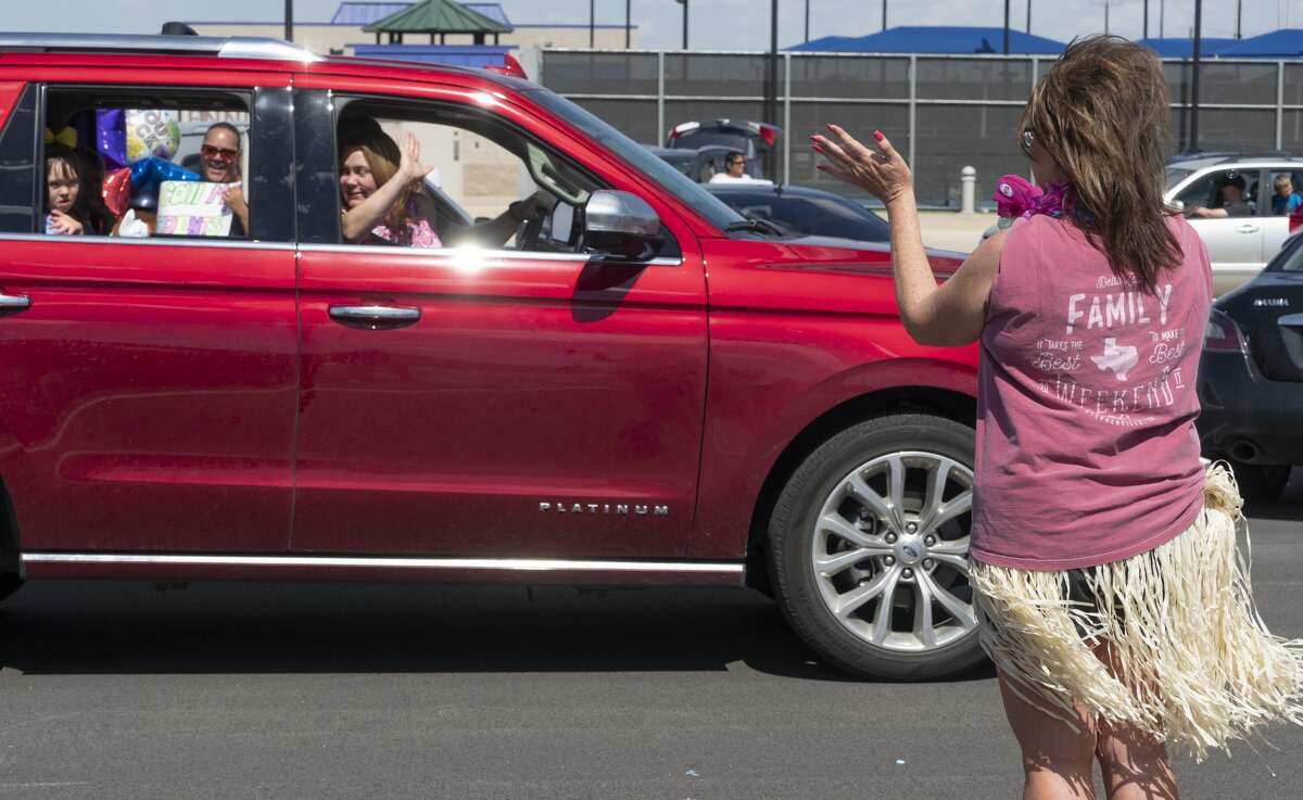 Bynum School administrators and teachers wave and hold signs as their students are driven past 04/28/2020 through the parking lot at Bush Tennis Center. Tim Fischer/Reporter-Telegram