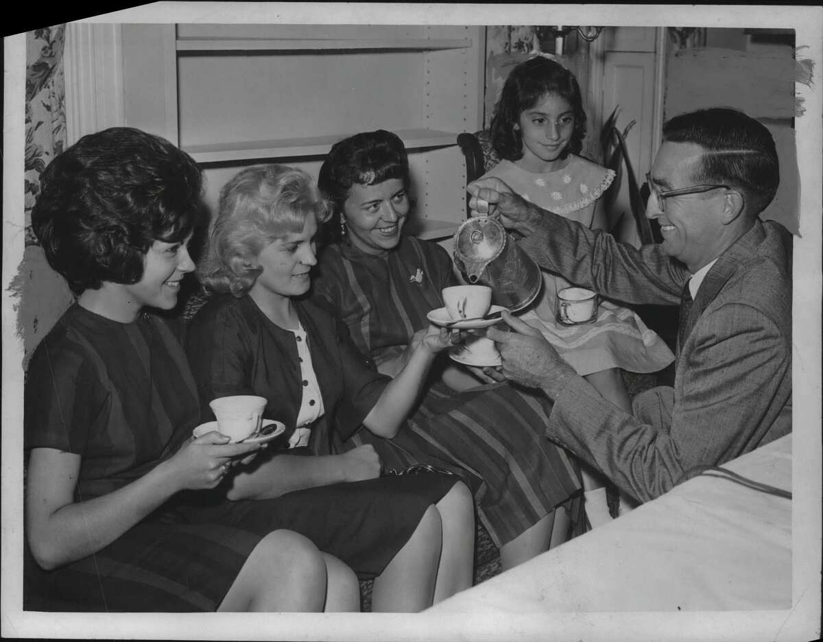 Lowell R Palmes, naturalization officer, pours tea for four new citizens following Citizenship Day naturalization hearings in Albany, New York. From left: Miss Irene M Szczepniak, Castleton, from Poland; Mrs. Terez Hajdn, Hudson from Hungary; Mrs. Hedwig Forrest, Bennington, Vermont, from Germany; and Filomena Ferracane, 28 Corning Street, from Italy. September 8, 1962 (Knickerbocker News Staff Photo/Times Union Archive)