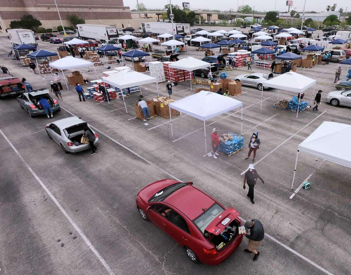 San Antonio Food Bank workers and volunteers load food into vehicles at the Alamodome on Friday, April 17, 2020.