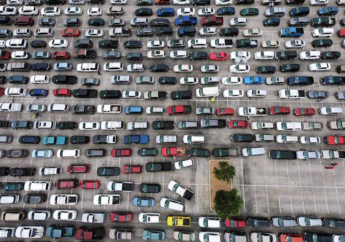 People in their vehicles line up at the Alamodome for a Food Bank distribution on Friday, April 17, 2020. About 2,200 families were expected to receive food.
