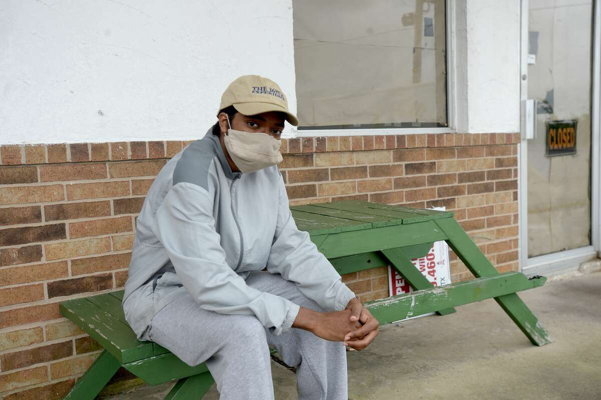 Jarrodd Henry sits outside the Green Acres Grocery as he waits for his father to finish shopping in Fannett, TX, Wednesday, April 22. Henry is back home with family i Winnie after his classes went online at A&M Prairie View, where he is studying music education. He says life now,