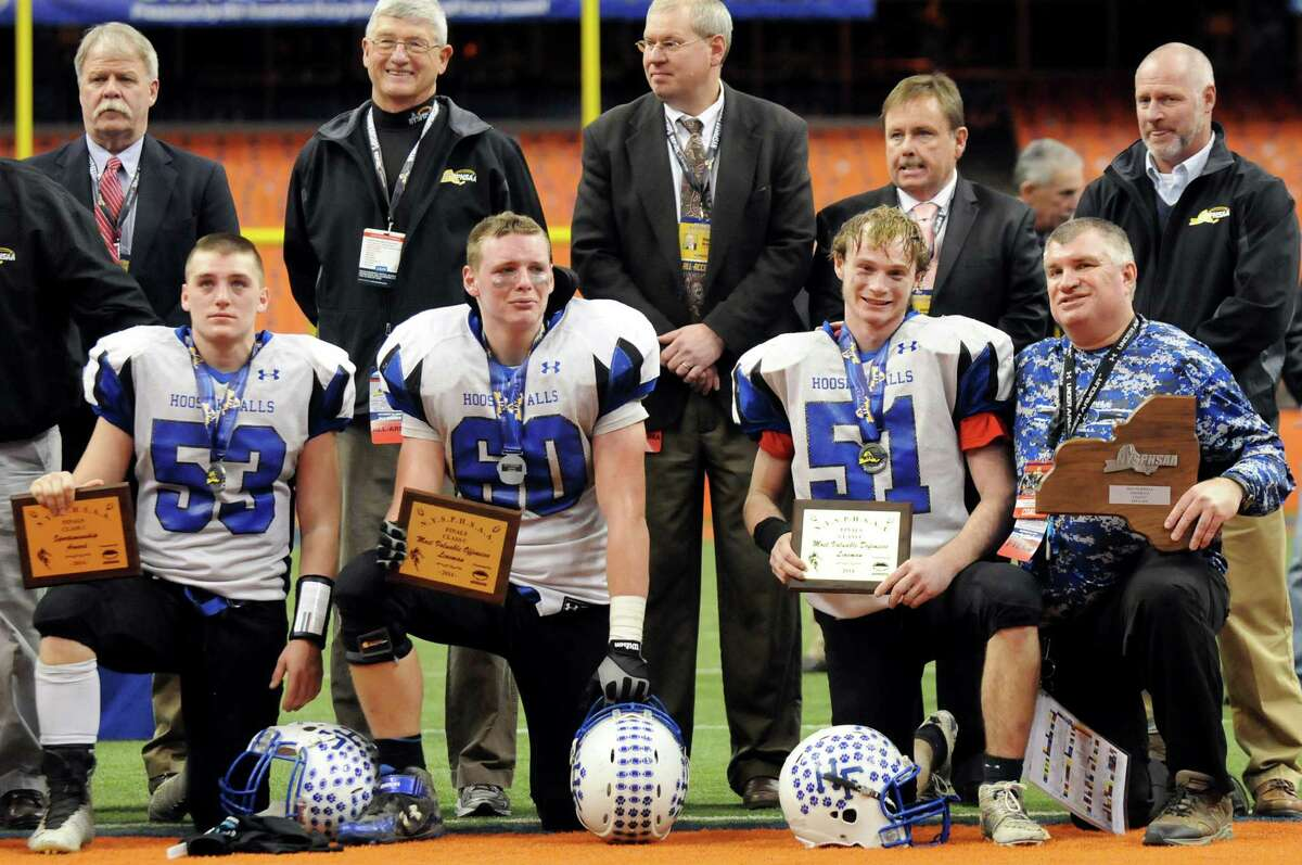 Hoosick Falls' players show mixed emotions as they pose with their awards with coach Ron Jones, right, and state football officials in a ceremony following their 20-14 loss to Chenango Forks in their Class C state football final on Saturday Nov. 29, 2014, at the Carrier Dome in Syracuse, N.Y. From left are Shayne Richard, Logan Hoyt and Jake Bakaitis. (Cindy Schultz / Times Union)