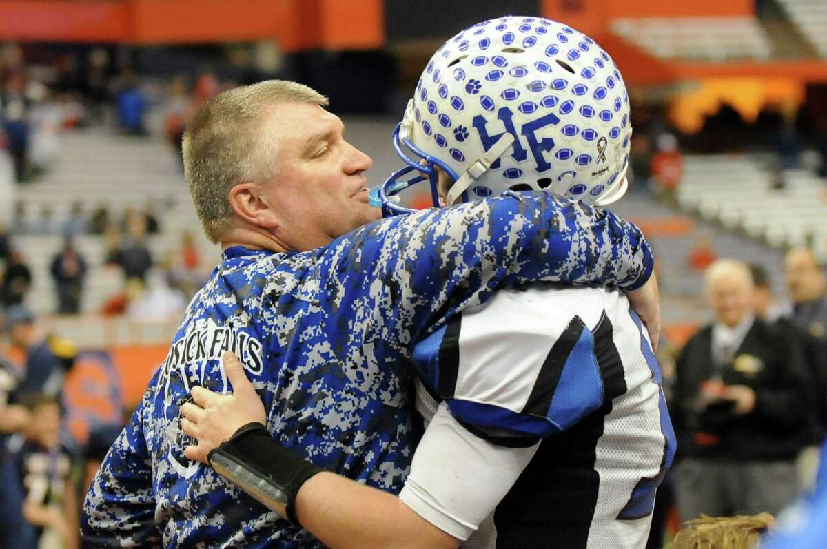 Hoosick Falls' coach Ron Jones, left, consoles quarterback Garrett Wright when they lose 20-14 to Chenango Forks in their Class C state football final on Saturday Nov. 29, 2014, at the Carrier Dome in Syracuse, N.Y. (Cindy Schultz / Times Union)