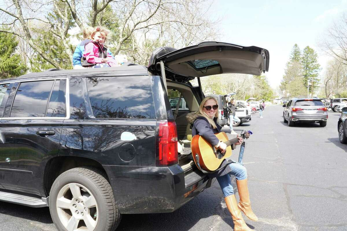 The music teacher for the First Presbyterian Nursery School, Meghan Gould, attended as a preschooler, plays the guitar outside of the school recently. Her children are in the sunroof - Madeline and Austin. Pre-K teacher Jenny Coutts is in the background on the left. They all recently attended a drive-by event at the school.