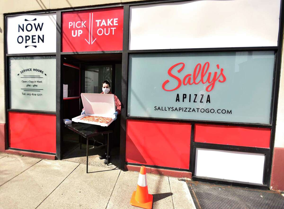 Francesca Messina, cashier at Sally's Apizza's shows a pizza at the pick-up and take-out area at the New Haven pizzeria.