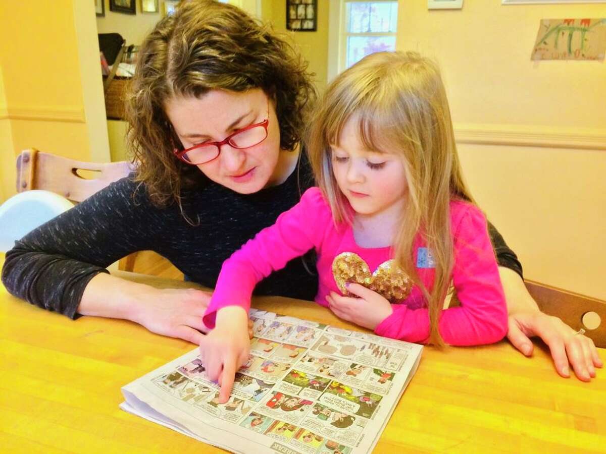 Laura Bower-Phipps and her daughter, Betty, read the comics page. During this time of social distancing, Betty misses her friends and school.