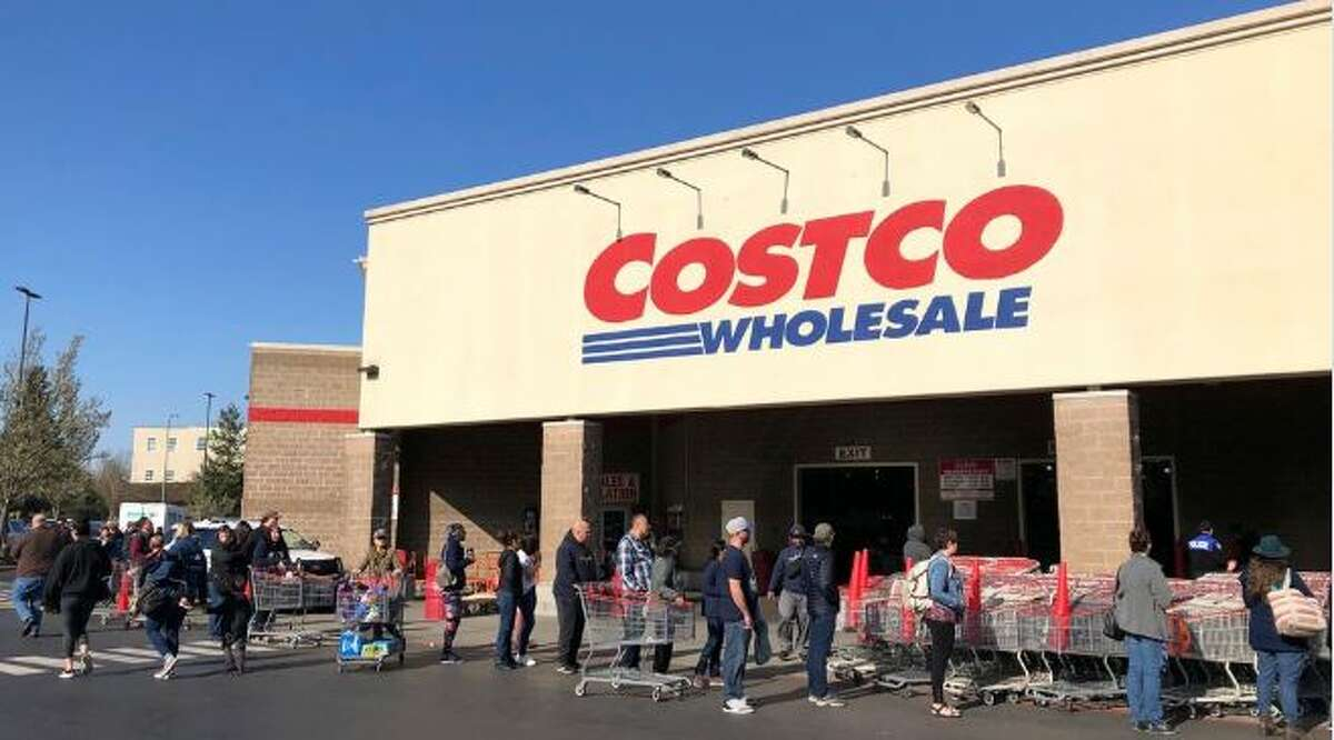In this March 20, 2020 file photo, shoppers line up to enter a Costco store in Tacoma, Wash.