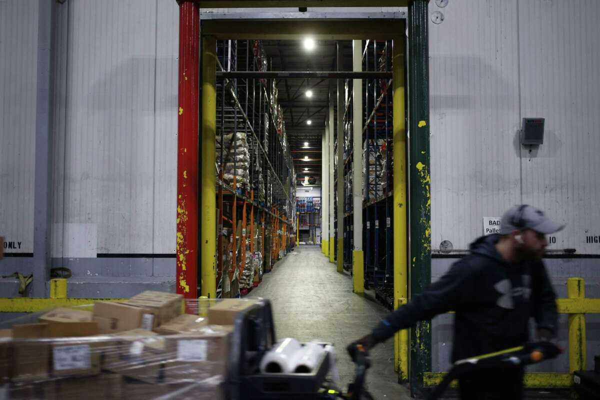 A worker drives a forklift through a grocery distribution center in Louisville, Ky., on March 20, 2020.