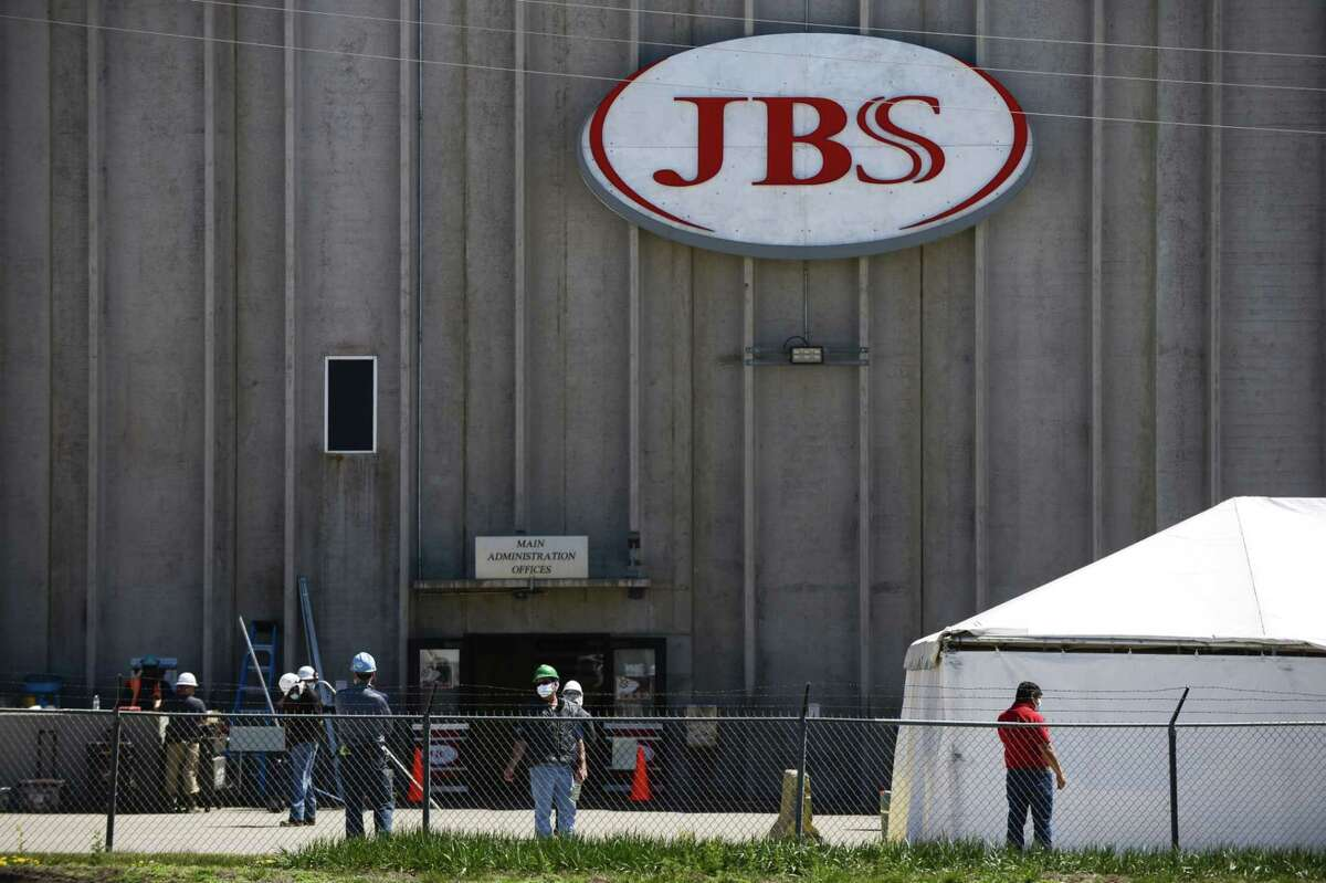 Workers wearing masks stand outside the JBS USA beef processing facility in Greeley, Colo., on April 27, 2020.