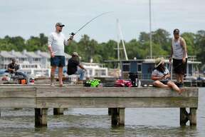 People fish off boat docks on Lake Conroe, Saturday, April 25, 2020, in Conroe.
