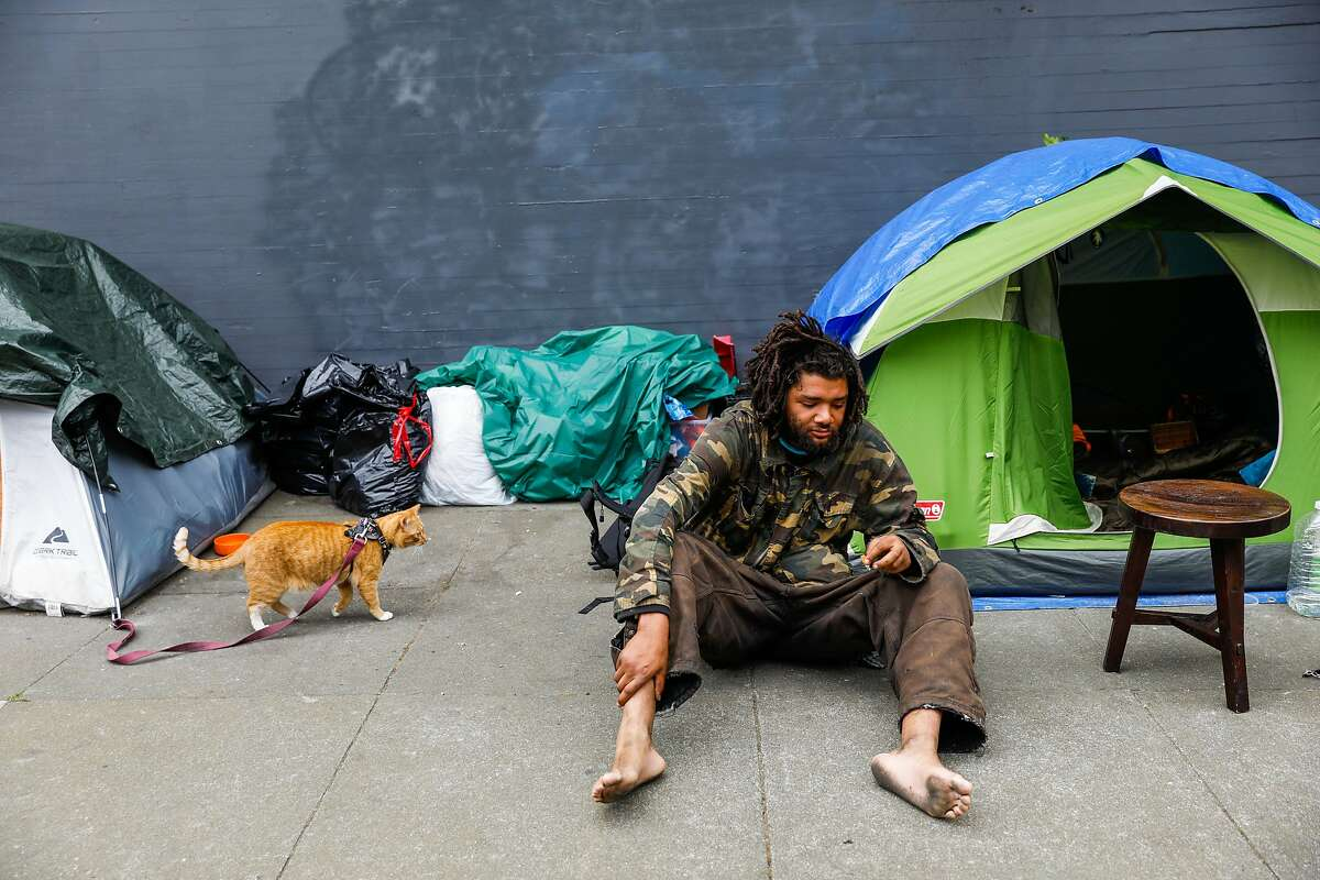 Damian William Pierce rests outside his tent on Waller Street on Sunday, April 19, 2020 in San Francisco, California.