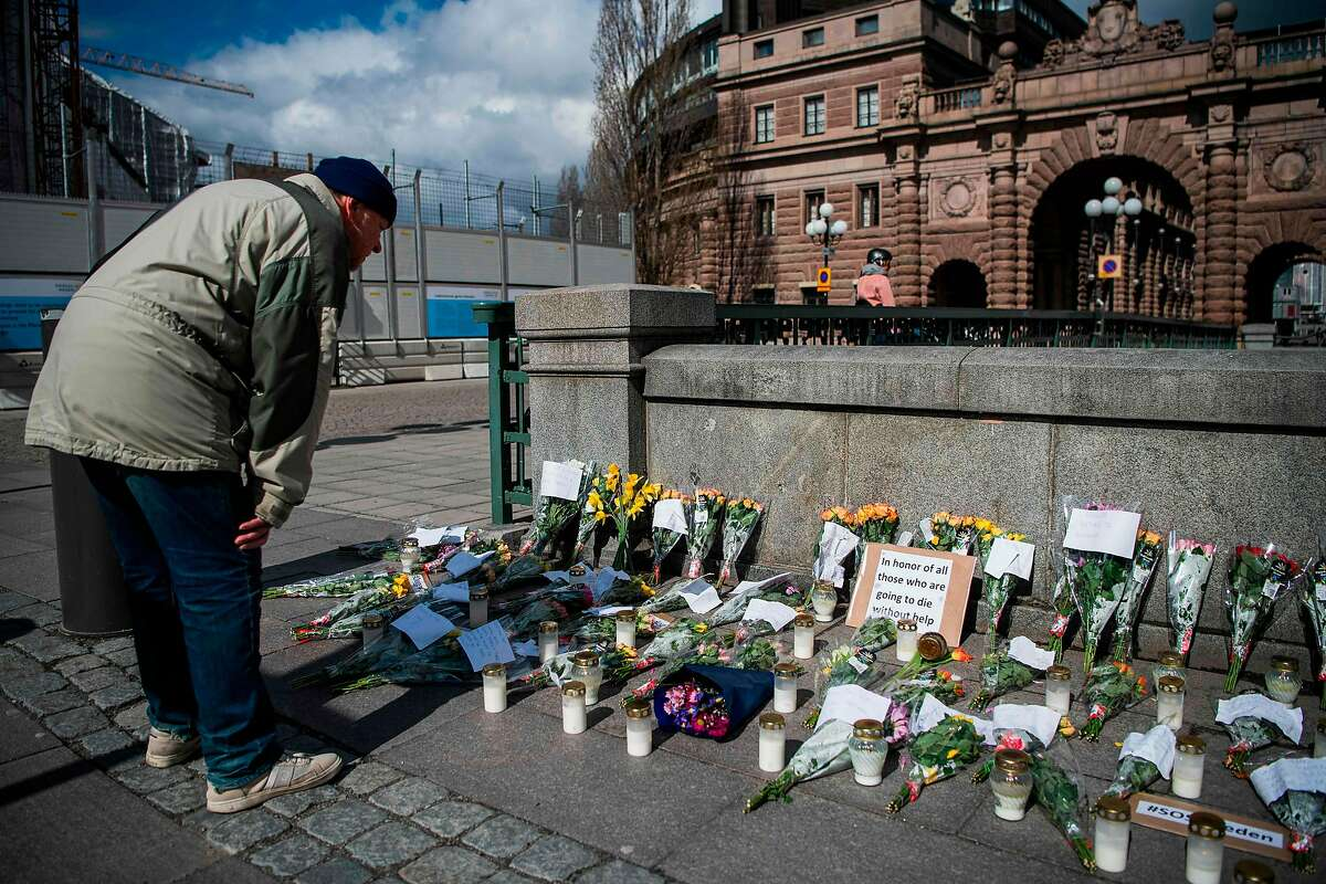 A memorial in Stockholm's Mynttorget Square in memory of loved ones lost to the new coronavirus features candles, flowers and handwritten notes, some of which express frustration over Sweden's softer approach to curbing the illness.