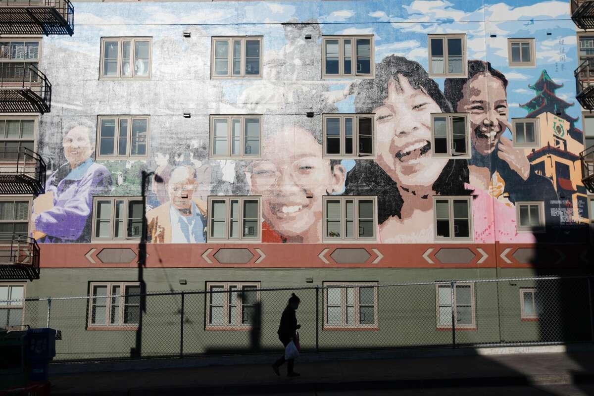 A masked woman walks down Stockton Street in San Francisco, Calif. on April 28, 2020.