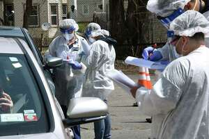 Health care workers are seen taking down personal information from drivers at a coronavirus testing site at the Washington Irving Education Center on Wednesday, Tuesday, April 29, 2020 in Schenectady, N.Y. (Lori Van Buren/Times Union)