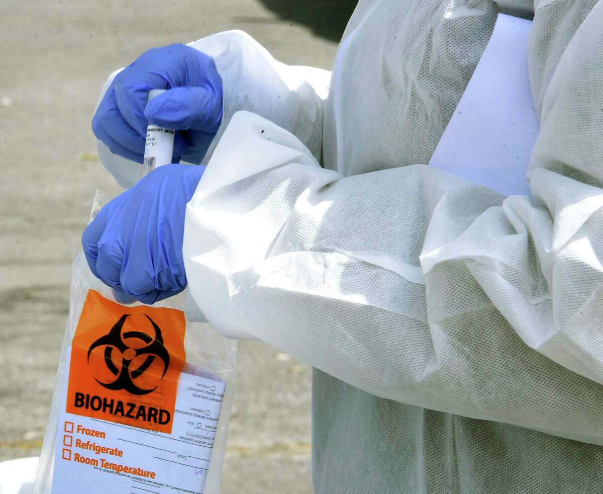 Ellis Hospital health care worker Sam Westbrook is seen putting a sample from a person into a biohazard bag at a coronavirus testing site at the Washington Irving Education Center on Wednesday, Tuesday, April 29, 2020 in Schenectady, N.Y. (Lori Van Buren/Times Union)