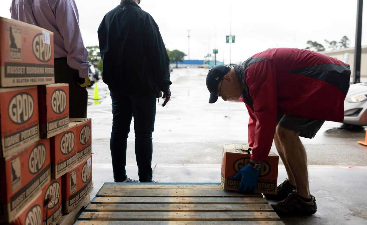 Robert Bardshaw prepares to take a food box to a vehicle at the Church Project in The Woodlands, Wednesday, April 29, 2020. The Church Project in collaboration with the Montgomery County Food Bank prepared food packages for up to 300 families.