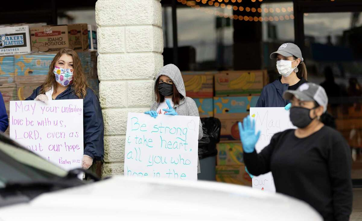 From left to right, Ashlie Bickford, Sofia Hall and Dea Taylor hold signs of inspiration at the Church Project in The Woodlands during a food distribution drive, Wednesday, April 29, 2020. The Church Project in collaboration with the Montgomery County Food Bank prepared food packages for up to 300 families.