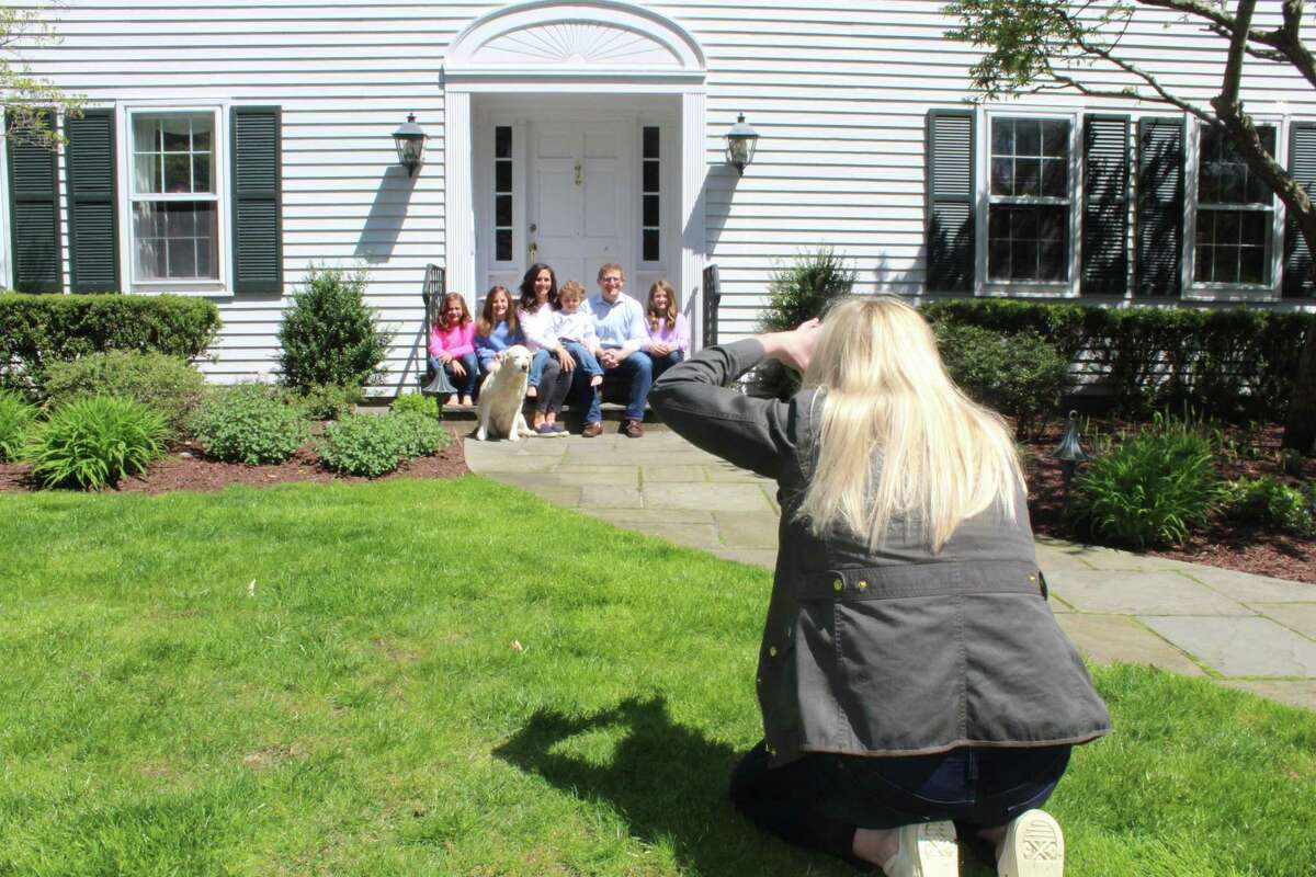 Meghan Murphy Gould photographs the Schlafman family as part of The Front Steps Project in New Canaan recently. Gould brought the effort to take family photos from a safe distance to the town. With there being someday when the coronavirus pandemic will be over, families like the Schlafmans are currently obtaining something to remember their time together during the pandemic.