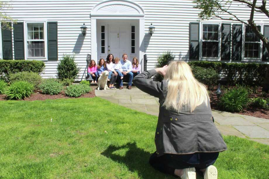 Meghan Murphy Gould photographs the Schlafman family as part of The Front Steps Project in New Canaan recently. Gould brought the effort to take family photos from a safe distance to the town. With there being someday when the coronavirus pandemic will be over, families like the Schlafmans are currently obtaining something to remember their time together during the pandemic. Photo: John Kovach / Hearst Connecticut Media / New Canaan Advertiser