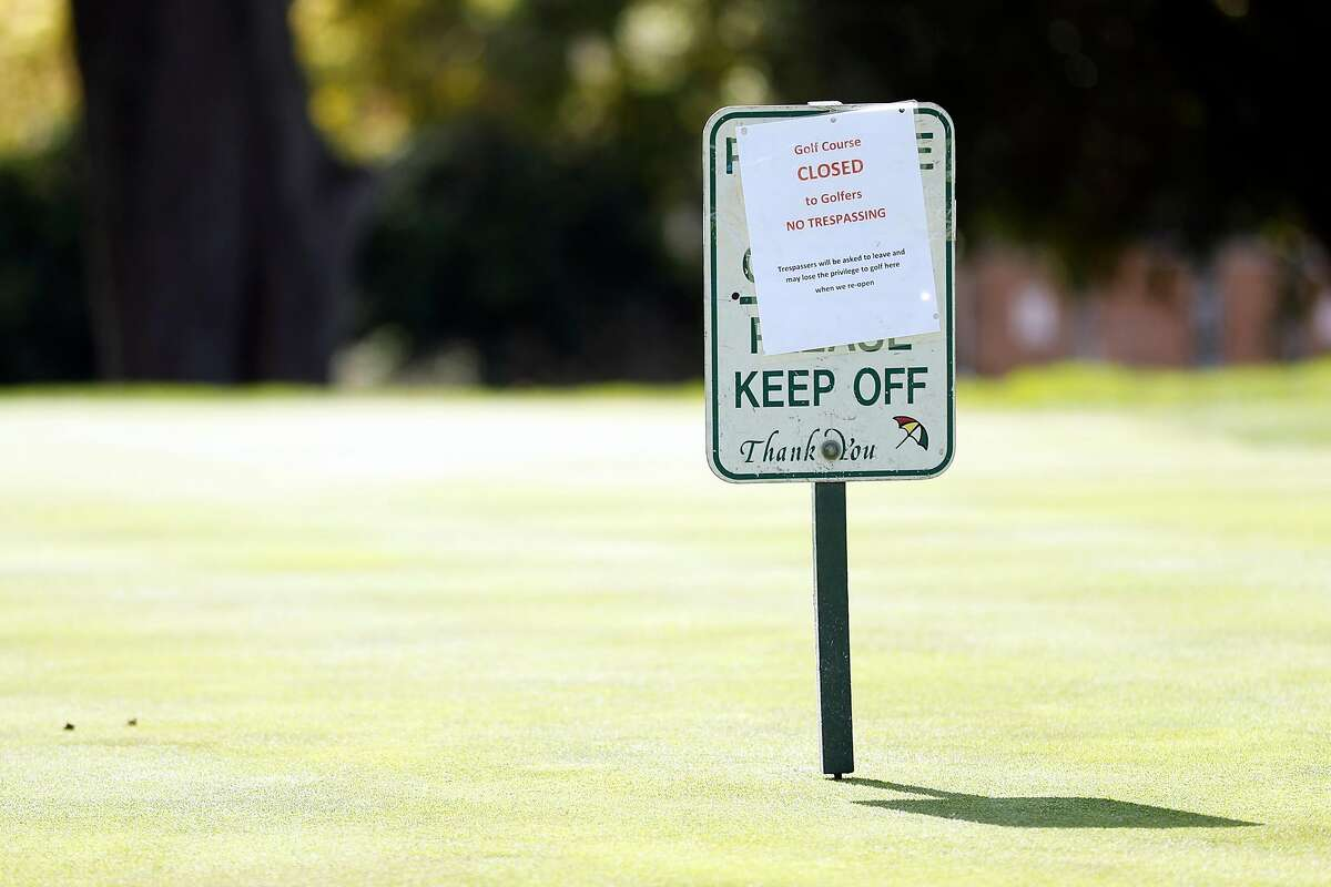 A closed sign on a green at Presidio Golf Course in San Francisco, Calif., on Monday, March 30, 2020.