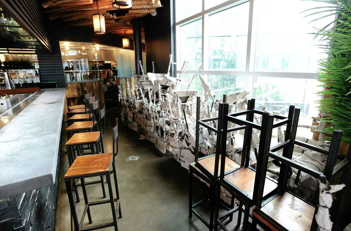 Chairs are stacked up at Mexicue restaurant in Stamford, Connecticut on April 29, 2020. The kitchen is busy preparing to go orders for customers living in Stamford's Harbor Point community. Several area restaurants like Mexicue, in response to the COVID-19 pandemic, have had to reinvent how they serve their customers and do business. Changing up menus, creating an online and social media presence. Mexicue has served over 350 meals weekly, as well as providing meals for frontline responders.