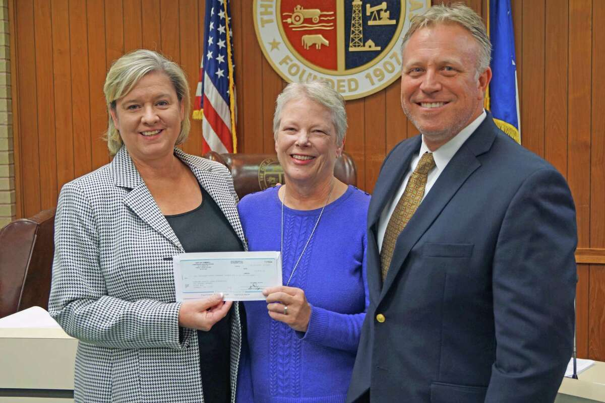 TOMAGWA executive director Judy Deyo receives a check for $10,836 from Tomball Mayor Gretchen Fagan and Assistant City Manager Rob Hauck during a recent meeting of the Tomball City Council.