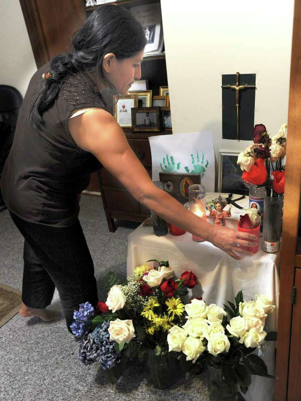 Sonia Zhunio tends to a memorial in her home for her son, Eric,4, who died after being hit by a truck in front of their Stevens Street home in Danbury.