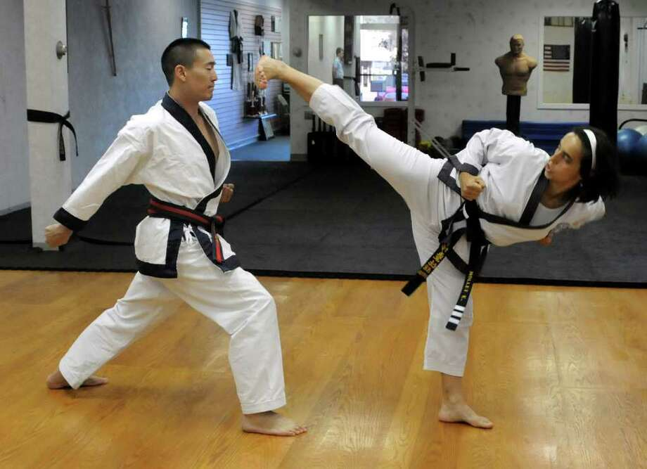 Frank Tsai, left, an instructor and fifth-degree master of Soo Bahk Do, and Elodie Mollet a third-degree master and instructor visiting from France, demonstrate kicks at Han Dol Martial Arts School in Danbury on Thursday Aug. 19, 2010. Photo: Lisa Weir / The News-Times Freelance