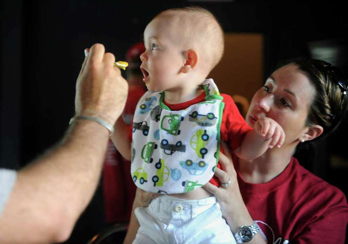 Steffanie Jurgens, right, holds her son, Jack, as her husband feeds him during a gathering for the team and supporters at the Bullfrog Brewery in Williamsport, Penn. Steffanie is a cousin of Fairfield player Nate Klein. The New England Champions defeated the Northwest in their game Friday, August 20, 2010.