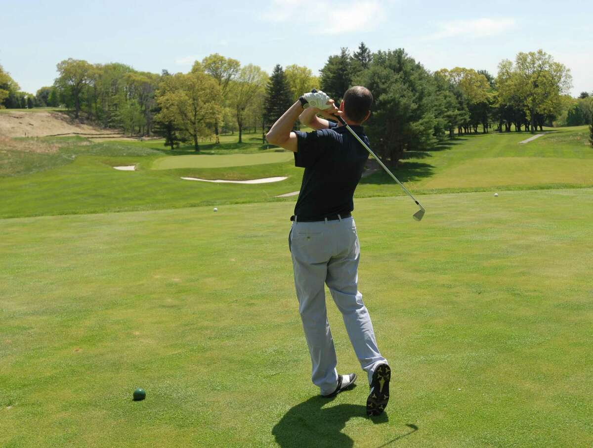 William Wallis, pro at the New Haven Country Club tees off on the 17th hole. Peter Casolino / New Haven Register